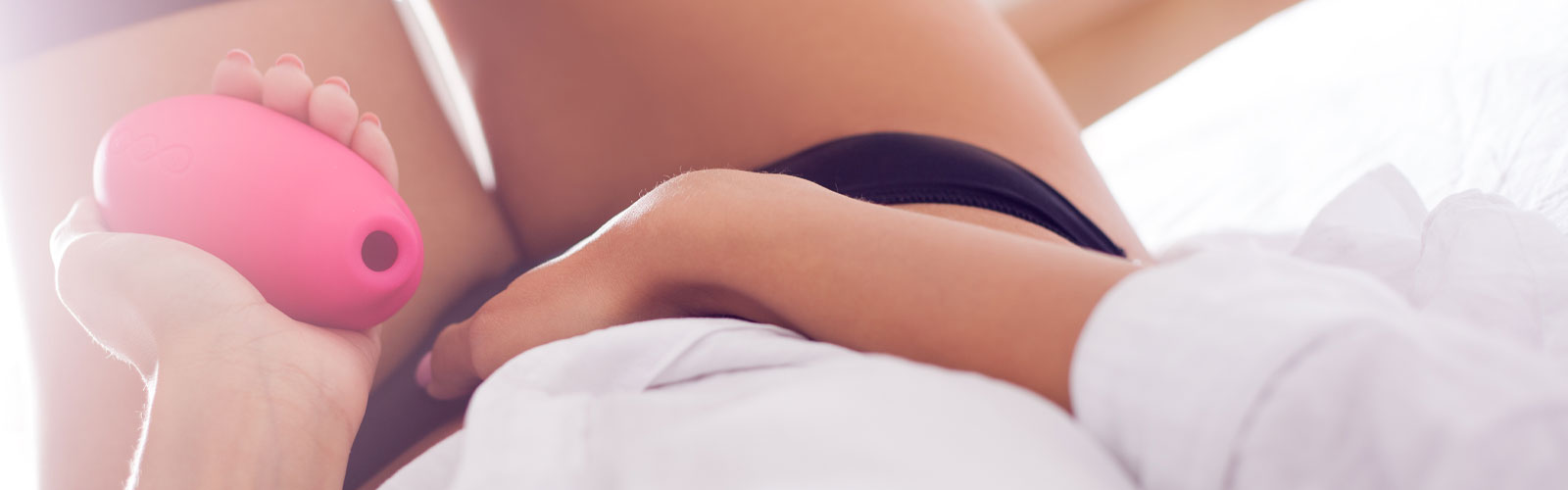 Woman holding clitoral stimulator in bed